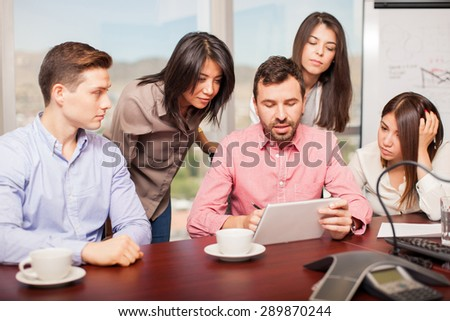 Handsome young man explaining something to a group of people with a tablet computer in a conference room