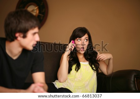 handsome young man feeling ignored by beautiful girlfriend on phone - stock photo
