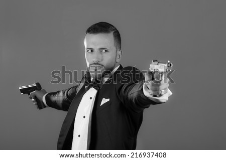 Handsome young man gangster police spy agent assissin holding and pointing with two guns wearing a suit black and white portrait - stock photo