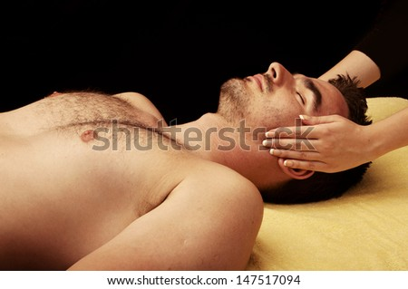 Handsome young man getting a face massage at spa - stock photo