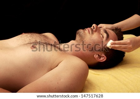 Handsome young man getting his face cleaned at spa - stock photo