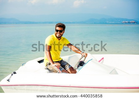 Handsome young man happy tanned, brunette driving a speedboat on the beach, wearing a yellow polo shirt, shorts, sunglasses, casual wear stylish lifestyle, beautiful smile, sunny day, tropical island - stock photo