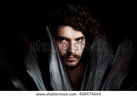 handsome young man hidden in a range of black leaves - stock photo