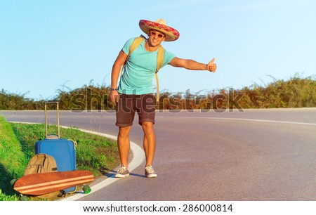 Handsome young man hitch-hiking along a rural mountain road - Hiker guy with luggage and longboard try to stop a car - Hand of hiker in a sunny day with copy space - stock photo