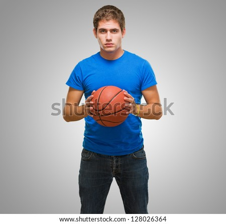 Handsome young man holding a basketball against a grey background - stock photo
