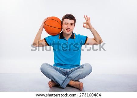 Handsome young man holding a basketball against a white background - stock photo
