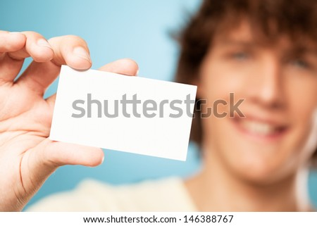 Handsome young man holding a blank card in front of himself.