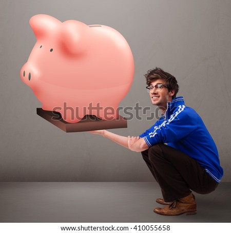 Handsome young man holding a huge savings piggy bank - stock photo