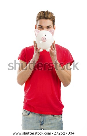 Handsome young man holding a piggy bank and smiling - stock photo