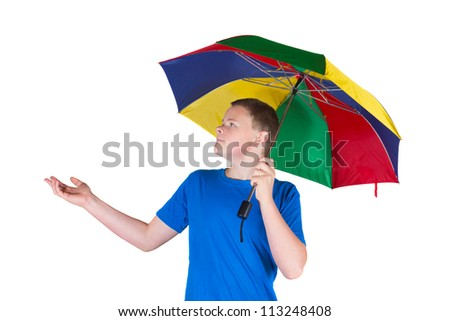 Handsome young man holding a rainbow coloured umbrella over his head for protection while extending his hand to check whether it is raining isolated on white