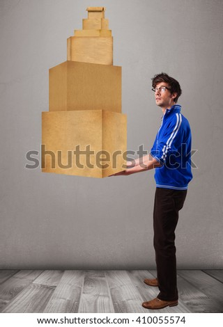 Handsome young man holding a set of brown cardboard boxes - stock photo