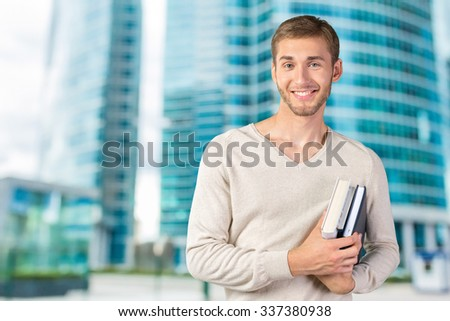 Handsome young man holding books - stock photo