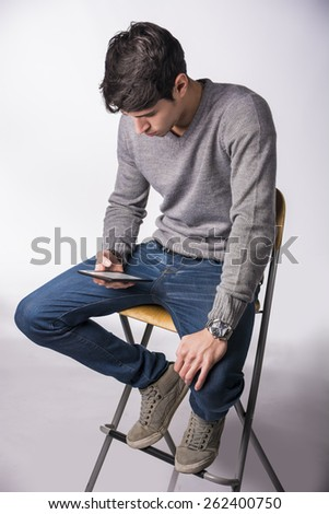 Handsome young man holding ebook reader and reading, sitting on white background - stock photo