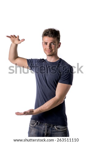 Handsome young man holding empty vertical space between hands for your product or text - stock photo