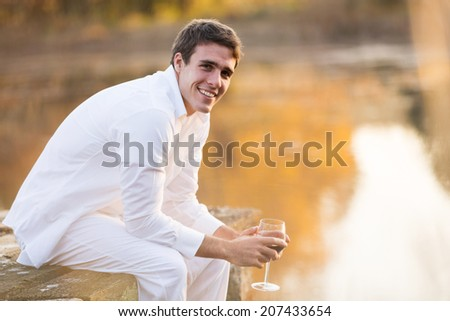 handsome young man holding glass of red wine by the pond - stock photo