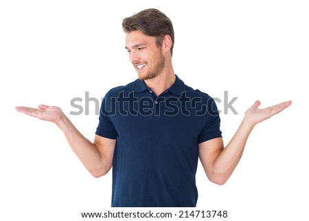 Handsome young man holding his hands out on white background - stock photo