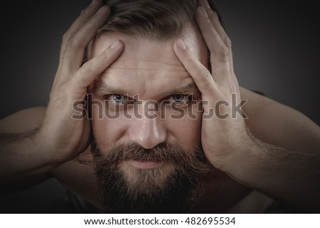 Handsome young man holding his head in hands over gray background