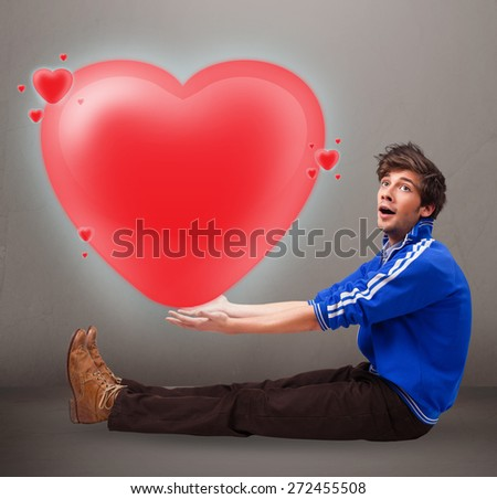 Handsome young man holding lovely 3d red heart - stock photo