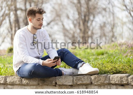 Handsome young man holding phone and enjoy the outdoors. Selective focus and small depth of field.