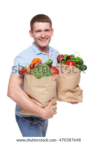 Handsome young man holding shopping bag full of groceries isolated at white background. Healthy food shopping. Paper package with vegetables and fruits, happy male buyer came from market