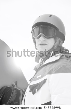 Handsome young man holding snowboard outdoors