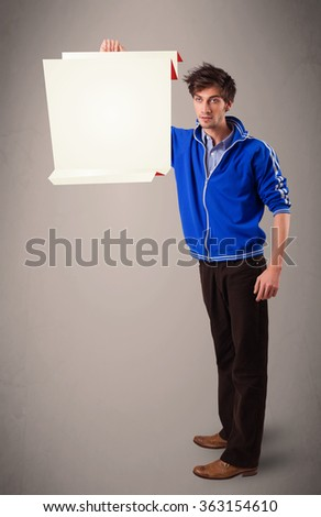 Handsome young man holding white origami paper copy space - stock photo