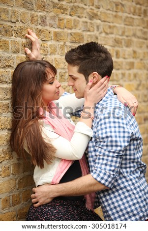 handsome young man hugging beautiful woman against brick wall - stock photo