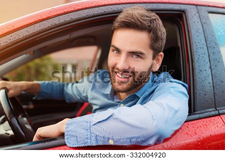 Handsome young man in a blue shirt driving a car - stock photo