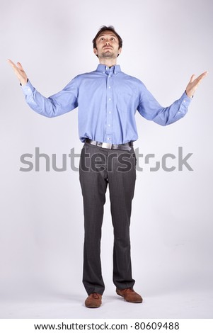 handsome young man in a blue shirt stands and looks up raising both hands to the sky - stock photo