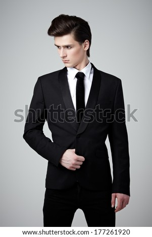 Handsome young man in a classic black suit on gray background