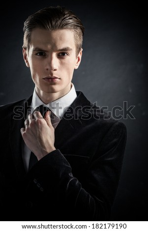 Handsome young man in a classic black suit on gray background - stock photo