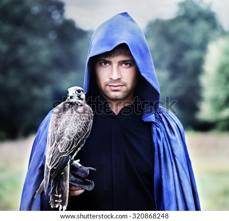 handsome young man in a raincoat with a falcon in his hand - stock photo