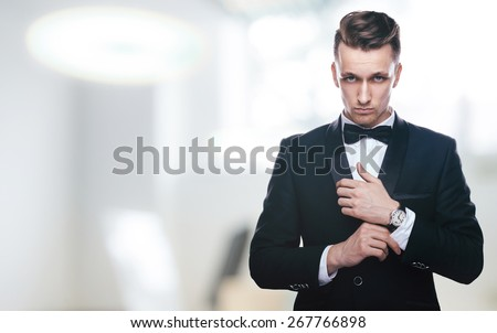 Handsome young man in a tuxedo looking at the camera. Fashionable Clothing. Clothing for the festive evening - stock photo