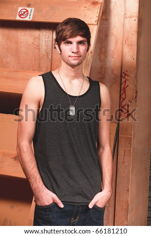 Handsome young man in an urban lifestyle pose in a loading dock area. - stock photo