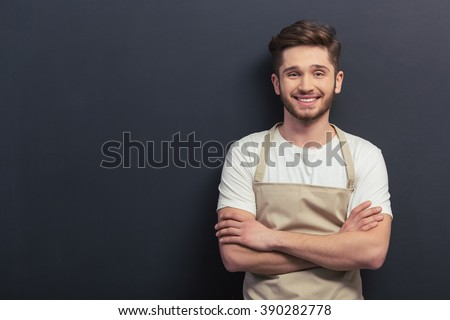 Handsome young man in apron is looking at camera and smiling, standing with crossed arms against blackboard - stock photo