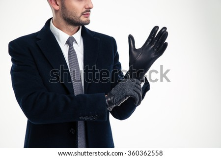 Handsome young man in black coat, white shirt and tie wearing leather gloves over white background - stock photo