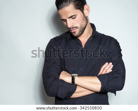 handsome young man in black dress shirt wearing a wristwatch  - stock photo