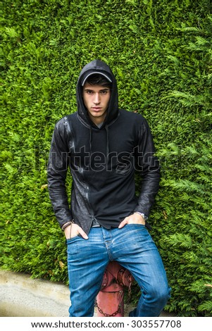 Handsome young man in black hoodie sweater standing outdoor against green plant hedge looking at camera - stock photo