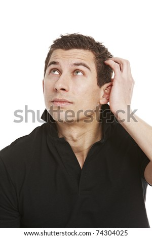 Handsome young man in black shirt looking up at corner of picture while scratching his head thinking about something