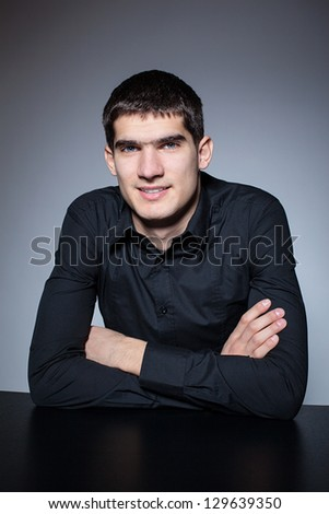 Handsome young man in black shirt on dark background.