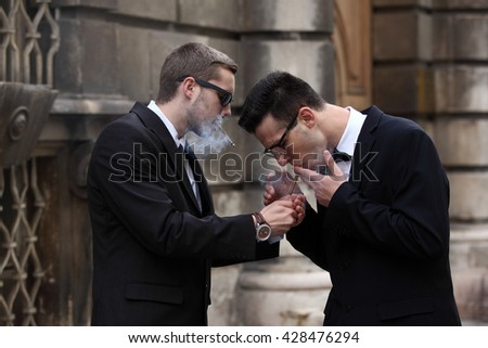 Handsome young man in black suit giving fire for his friend smoking a small cigar