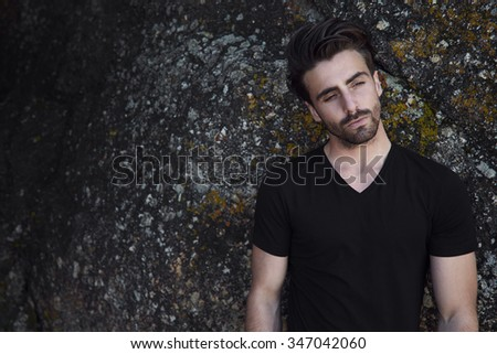 Handsome young man in black t-shirt against rock - stock photo