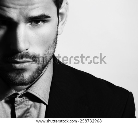 handsome young man in business suit posing on grey background - stock photo