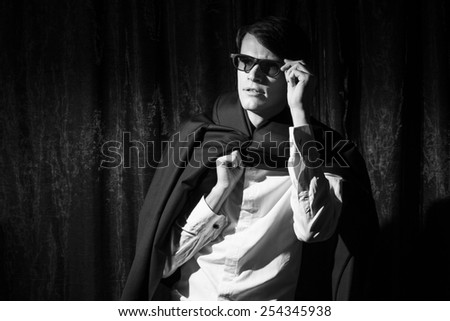 Handsome young man in business suit stay on drapes background. Holding glasses. Black and white portrait. - stock photo