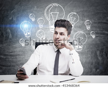 Handsome young man in business suit thinking about something in front of wall with sketch of lightbulbs on it. Concept of thinking - stock photo