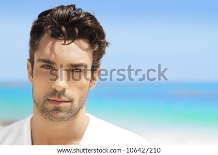 Handsome young man in casual white top against bright beach background - stock photo