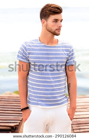 Handsome young man in casual white top at bright beach background in summer hot days,sailor,bearded man,tattoo man,stylish man looking for a woman walking on the beach alone,looking ,trendy guy,travel - stock photo