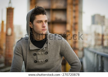 Handsome young man in city setting, with industrial site around him, looking away serious - stock photo