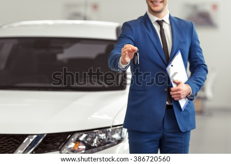 Handsome young man in classic blue suit is smiling, looking at camera and offering car keys while presenting car in a motor show, cropped - stock photo