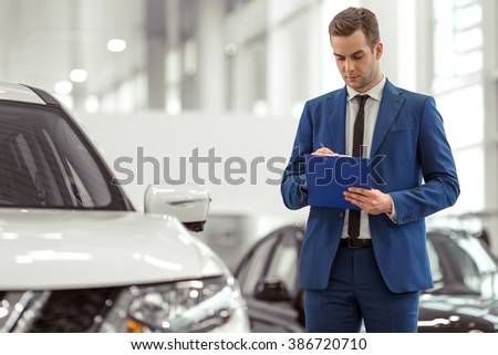 Handsome young man in classic blue suit is taking notes while examining car in a motor show - stock photo